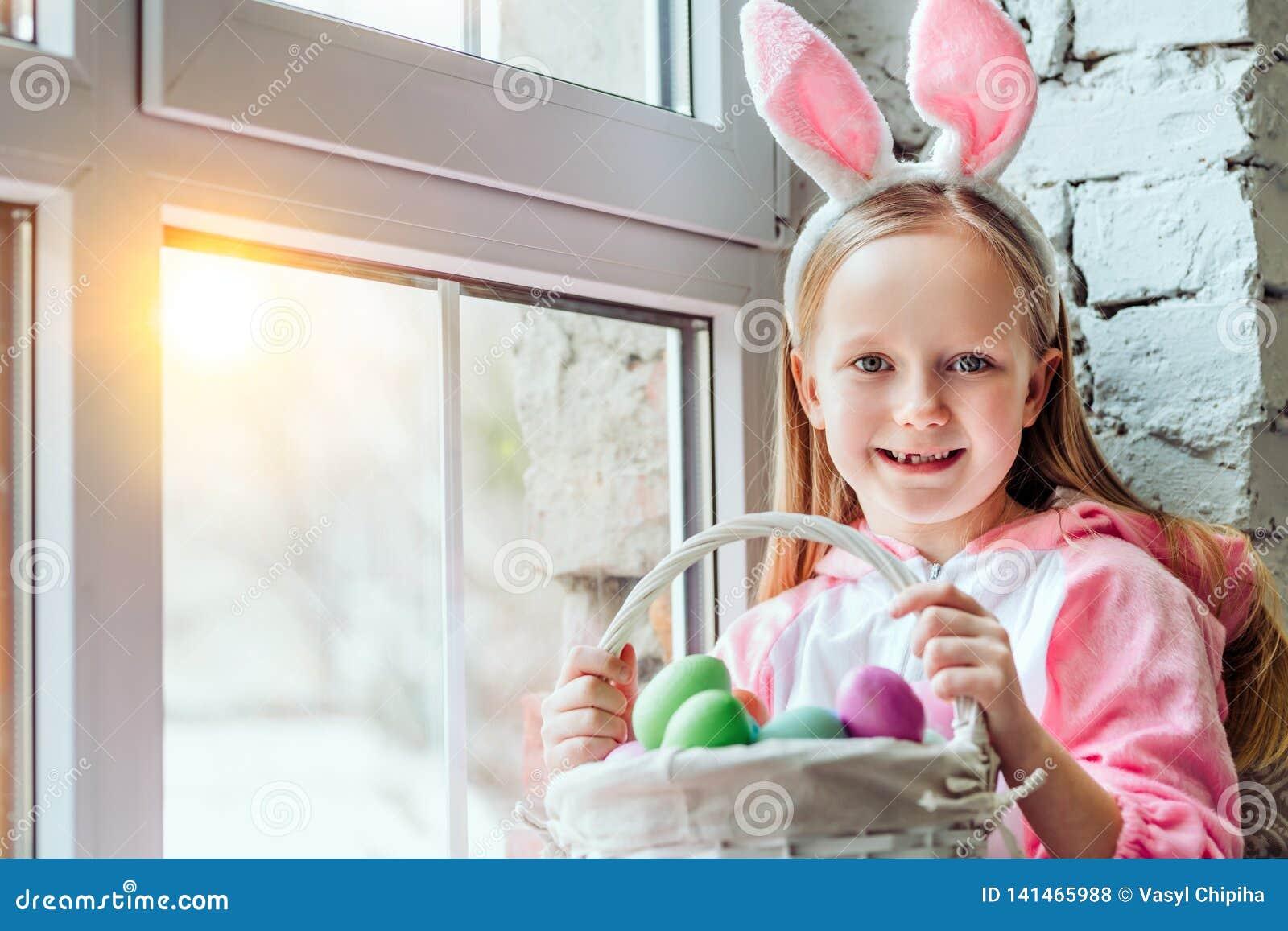 我爱复活节!兔子服装的美丽的女孩在家坐窗台并且拿着复活节彩蛋篮子