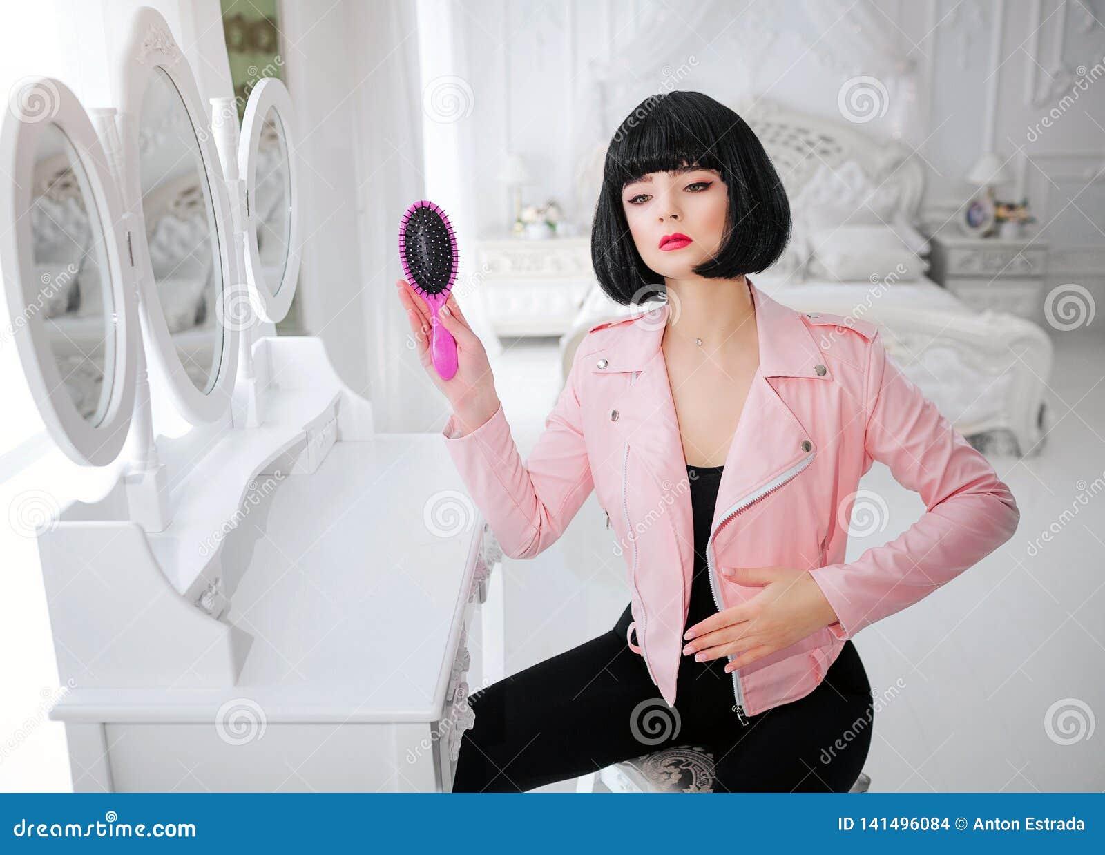 时尚畸形人 魅力综合性女孩、假玩偶有空的神色的和短的黑色头发举行桃红色发刷一会儿