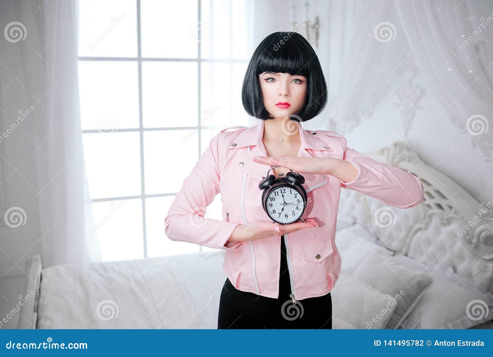 时尚畸形人 魅力综合性女孩、假玩偶有空的神色的和短的黑色头发拿着时钟,当站立时