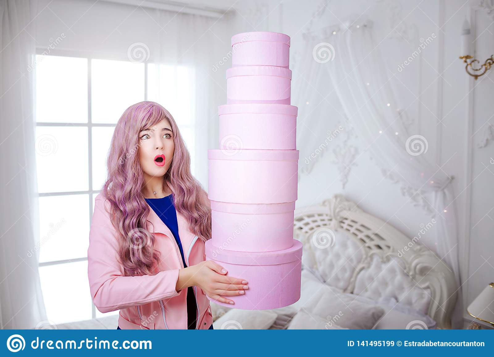 时兴的畸形人 有长的淡紫色头发的魅力情感美女拿着桃红色箱子,当站立在白色时