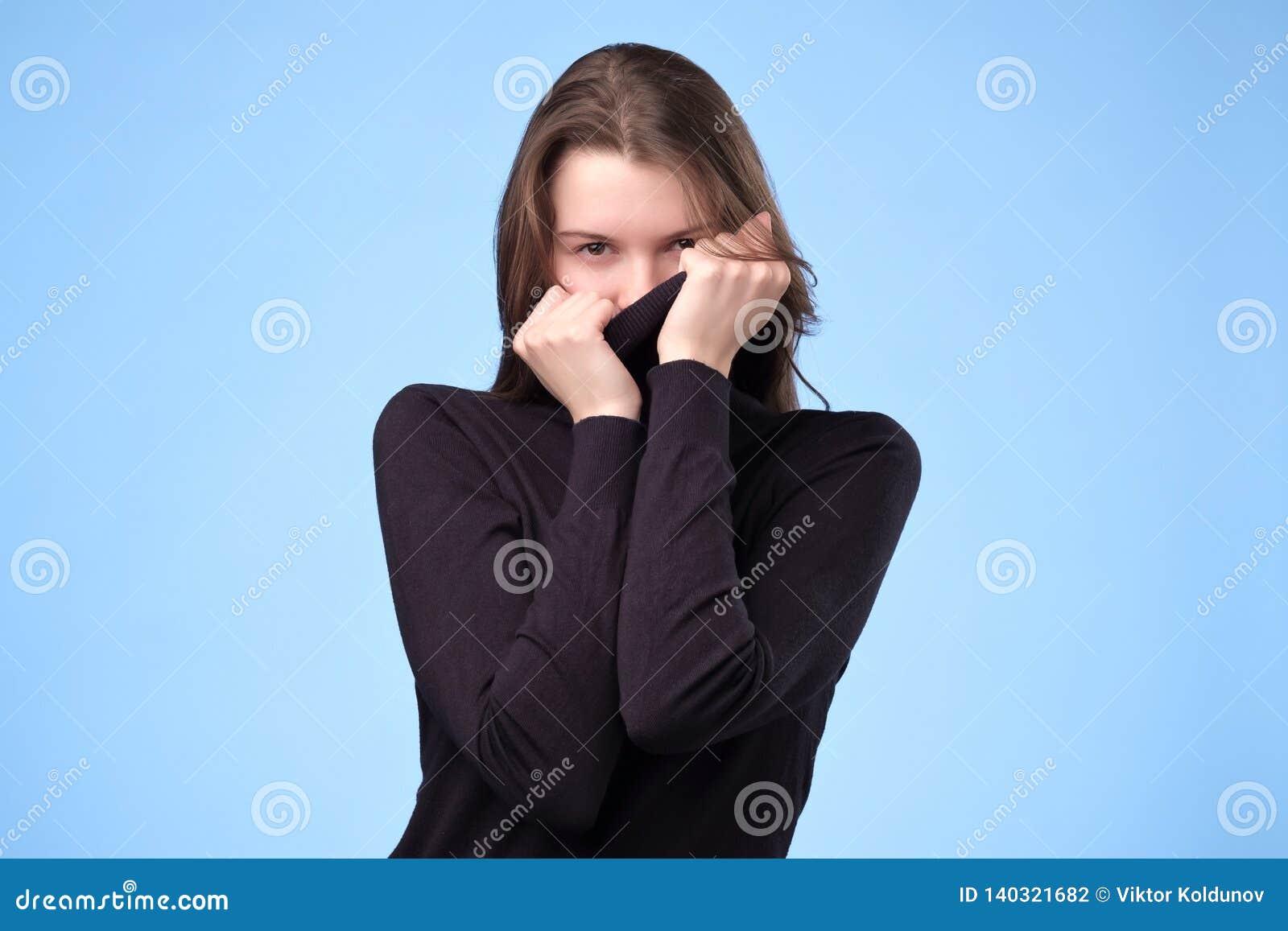 时髦蓝色毛线衣掩藏的面孔的快乐的妇女在它,在嬉戏的心情
