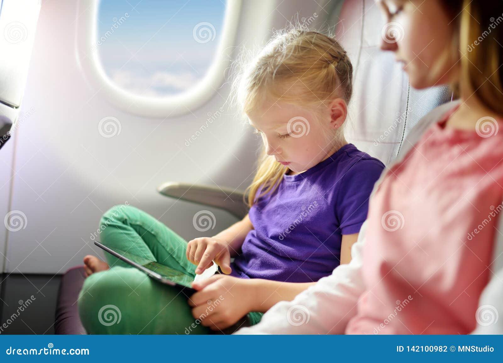 旅行乘飞机的可爱的小女孩 坐由航空器窗口和使用一种数字式片剂的孩子在飞行期间