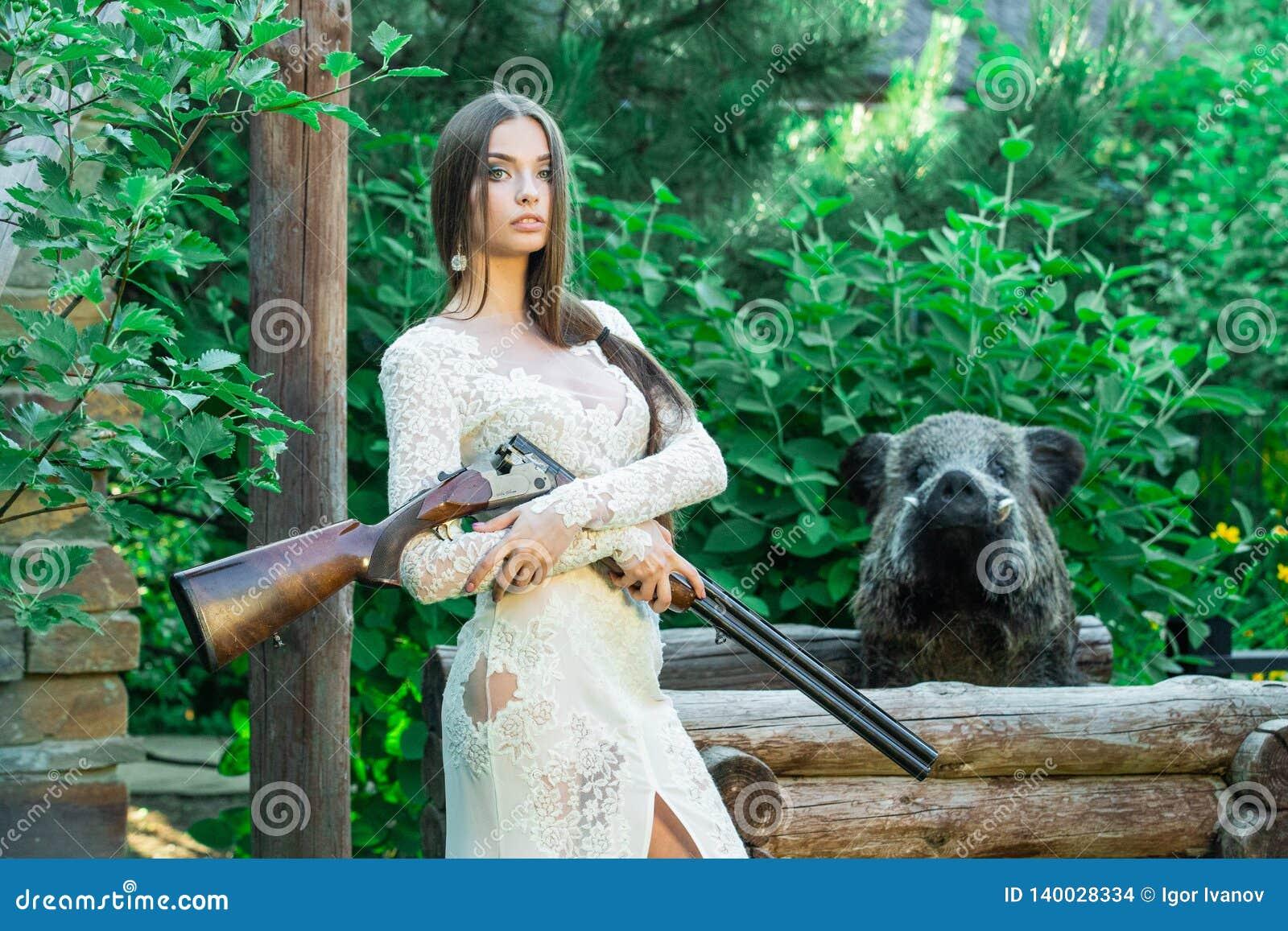 摆在与一头寻找的步枪和被充塞的公猪的白色礼服的美女在背景