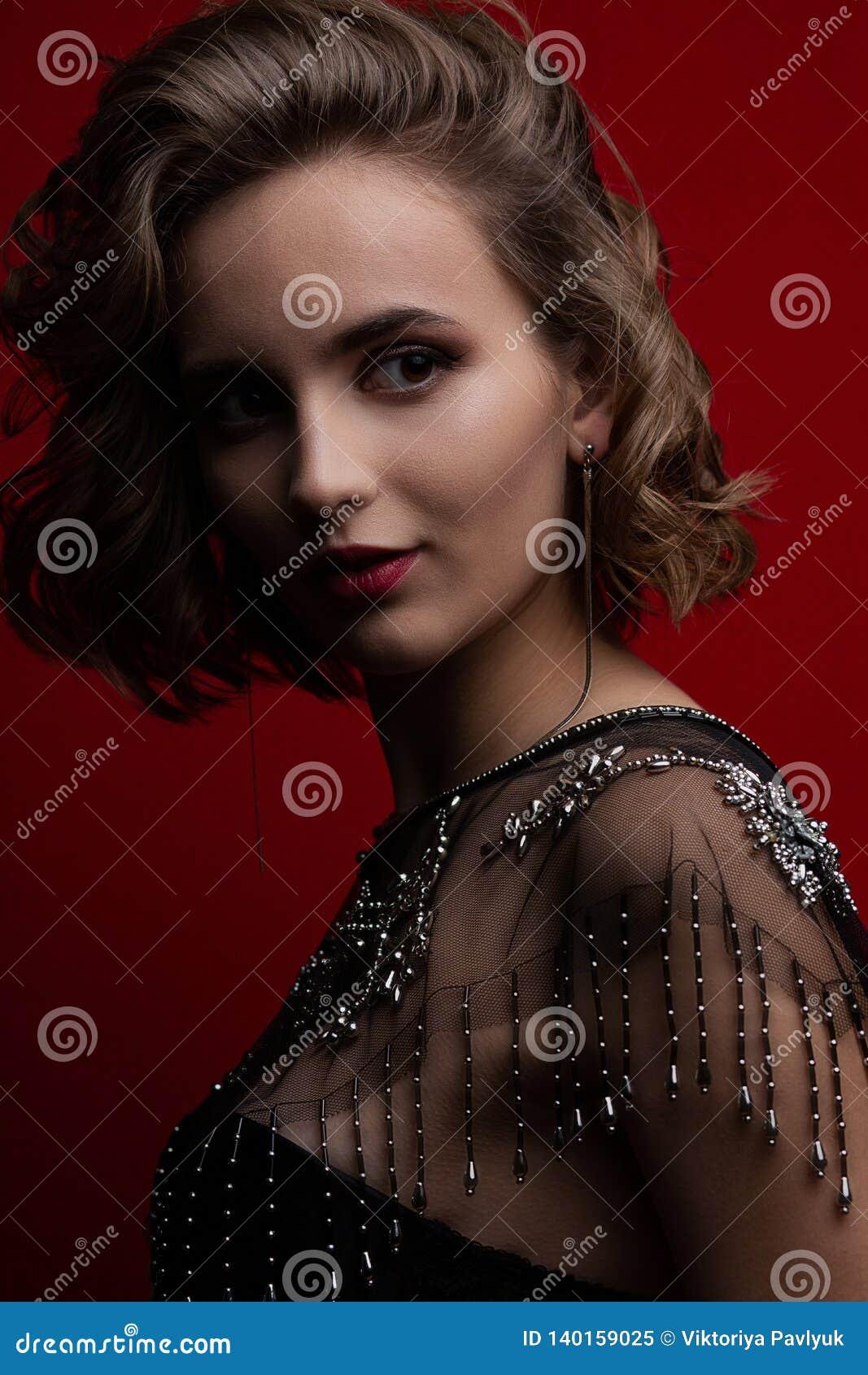 摆在与对比光的有吸引力的深色的模型特写镜头画象在红色背景