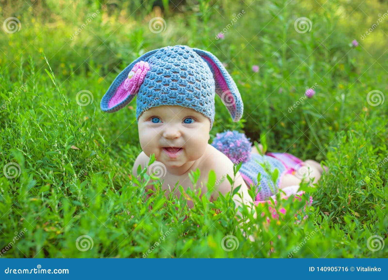 摆在象复活节兔子的微笑的婴孩孩子