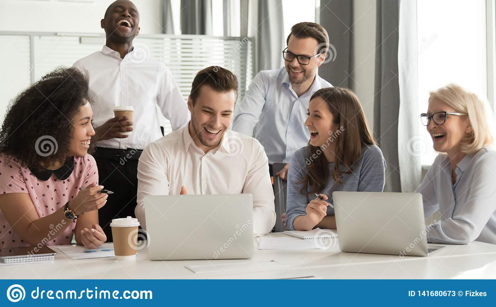 愉快的不同的办公室工作者合作一起笑在小组聚会上