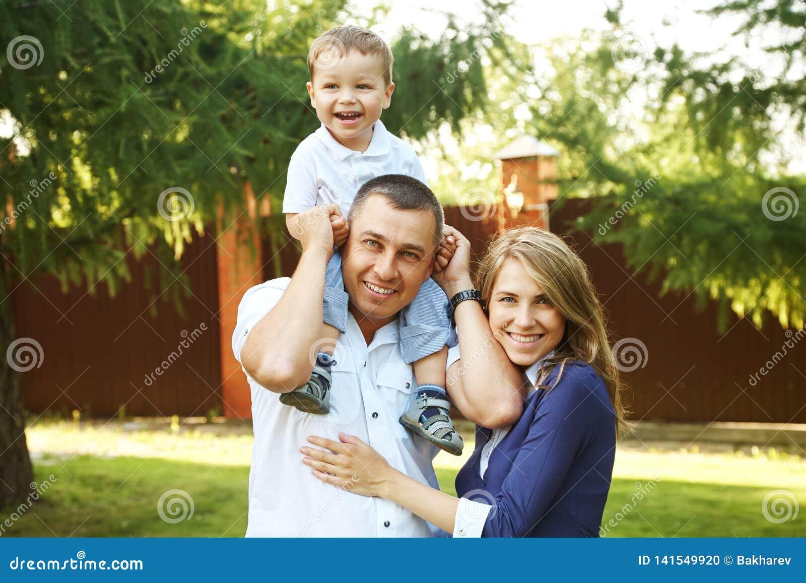 愉快的使用的家庭户外 有儿子的年轻父母在夏天 妈妈、爸爸和孩子