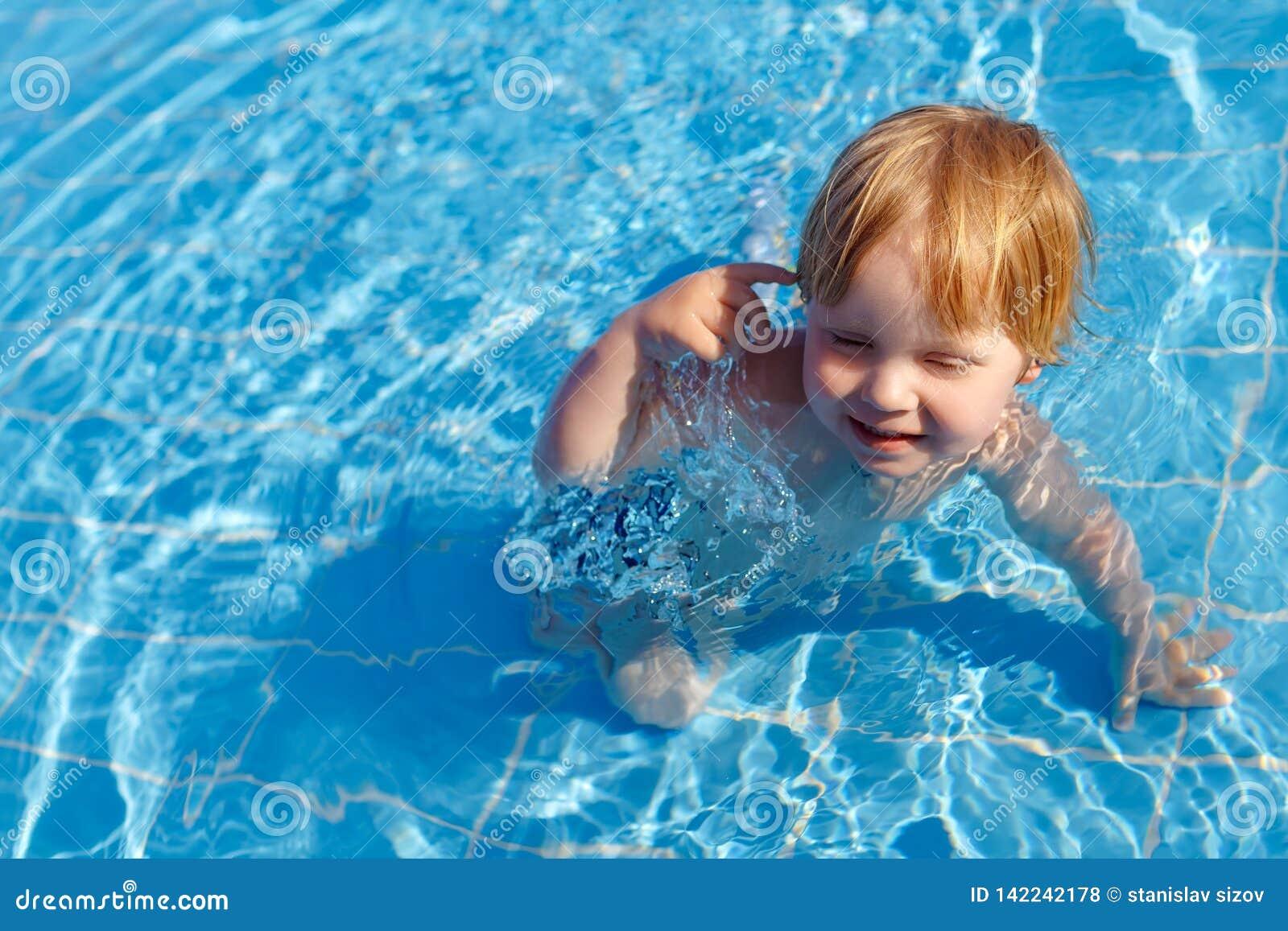 愉快的矮小的公平的儿童男孩在游泳场的水中