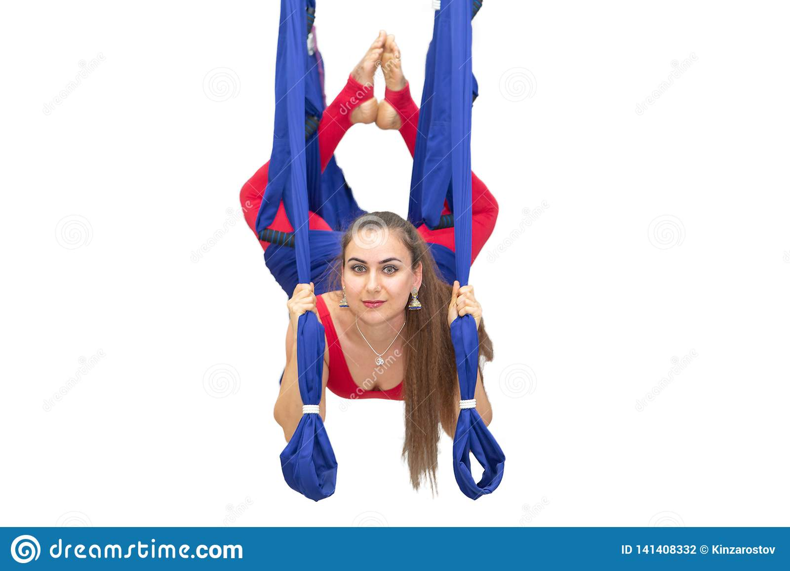 执行舒展妇女年轻人 健身、舒展、平衡、锻炼和健康生活方式人民 使用吊床的妇女