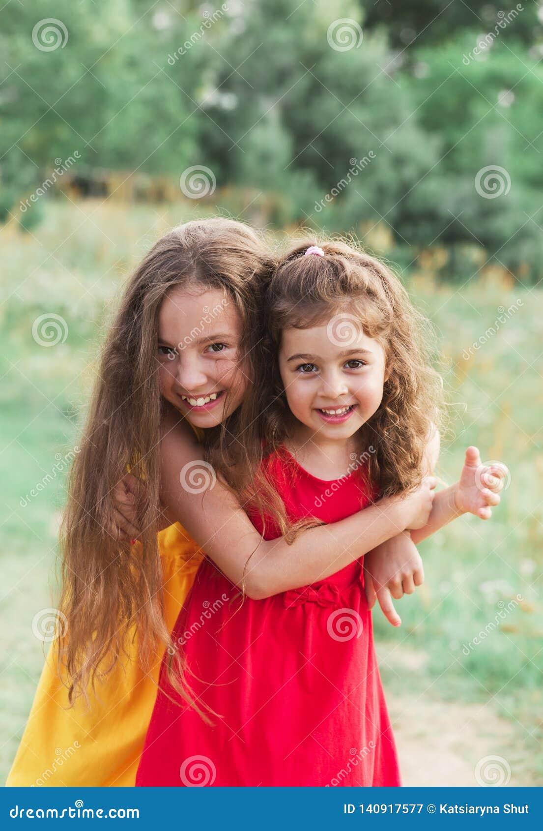 拥抱和嘲笑乡下的两逗人喜爱的女孩画象  愉快的孩子户外