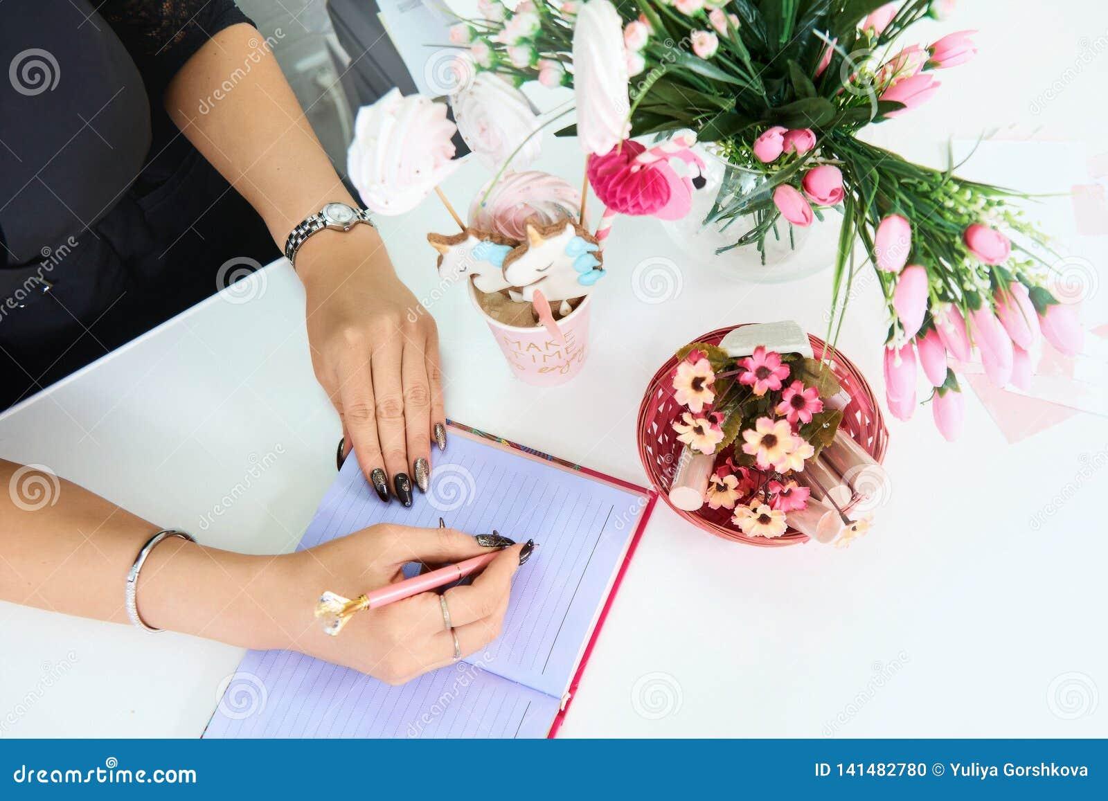 拿着笔的手欧洲女孩和写在一个空的笔记本 附近花和糖果