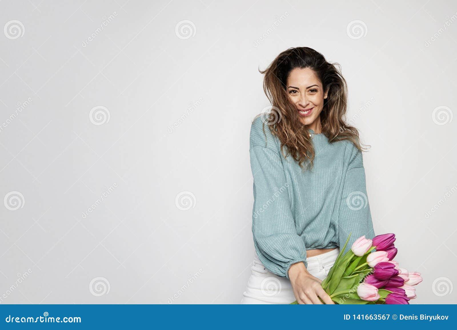 拿着色的郁金香花束的一微笑的年轻女人的画象被隔绝在灰色背景 复制浆糊空间