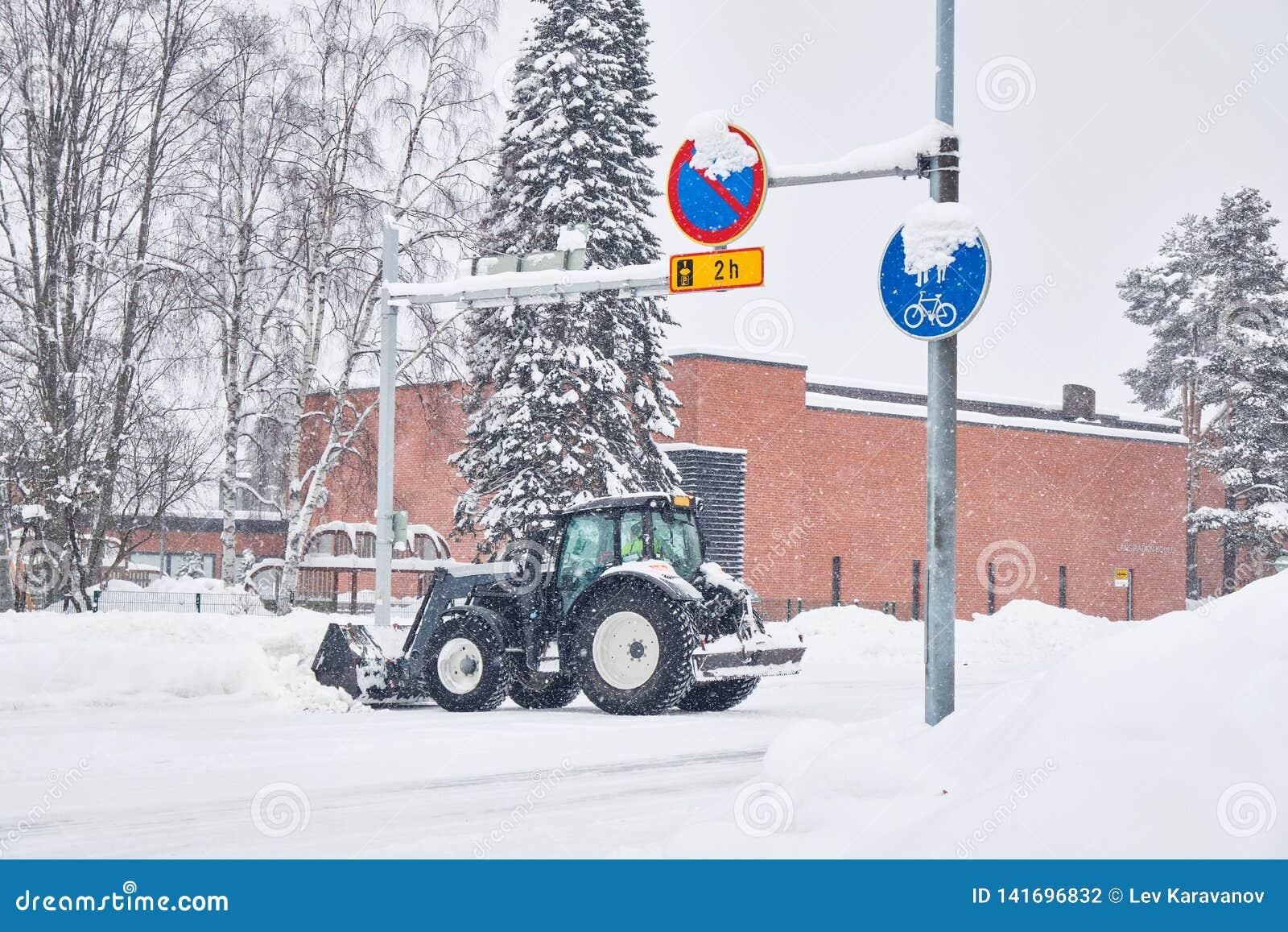 拖拉机在雪风暴以后的清洁街道
