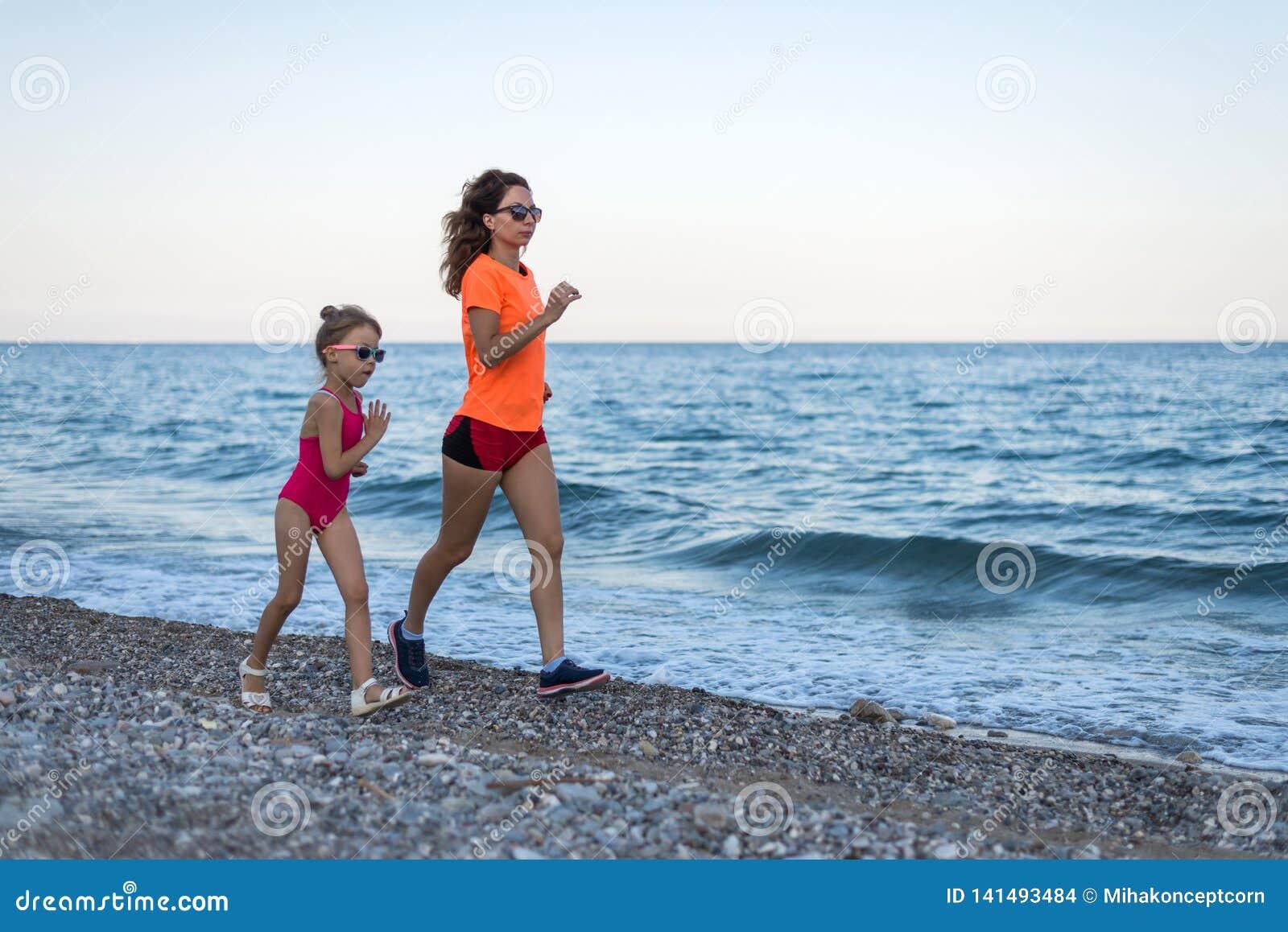 活跃生活方式:沿海滩的妈妈和女儿奔跑