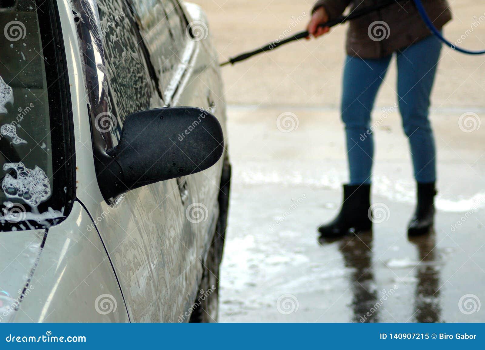 洗涤一辆白色汽车 妇女在背景中