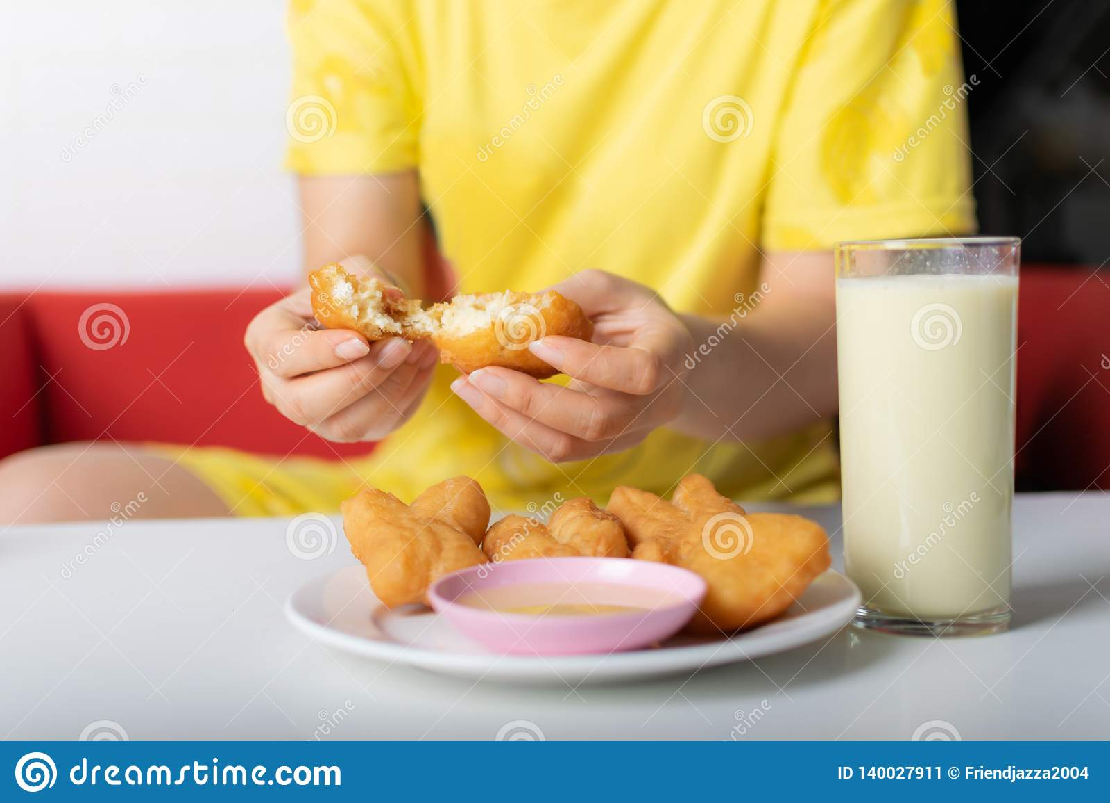 撕毁油煎的小圆面包的妇女的手在杯在桌上的豆浆附近