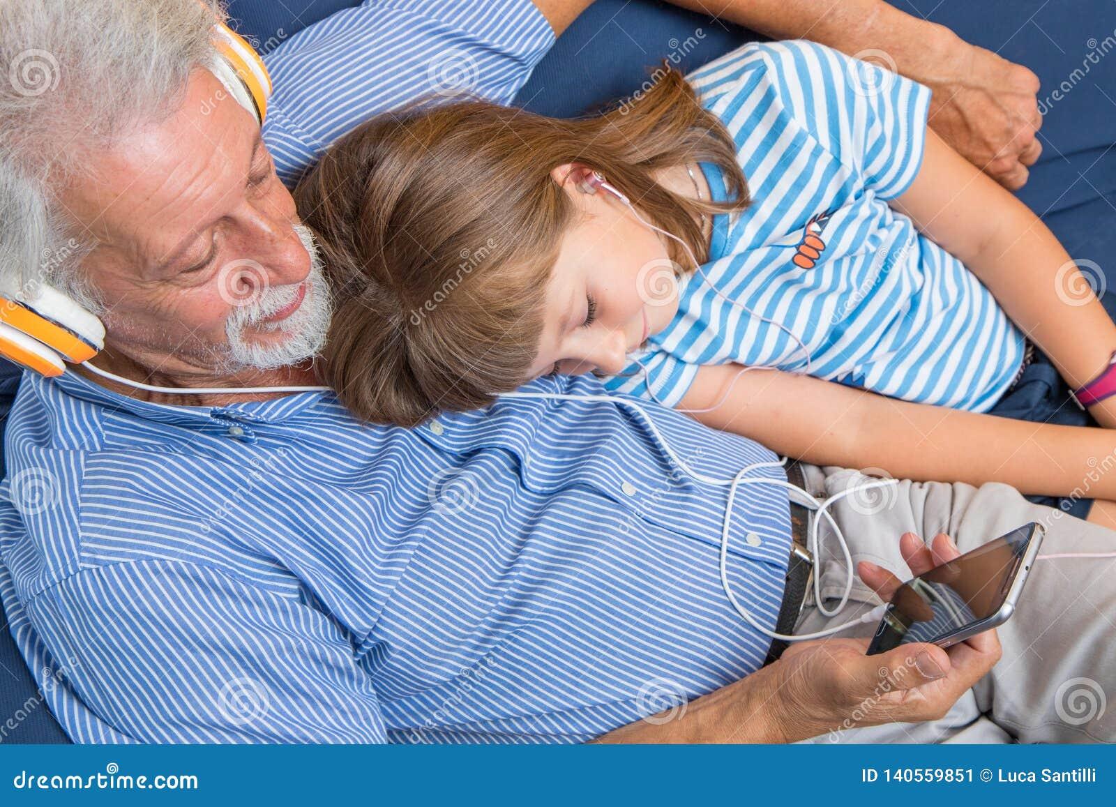 祖父和女儿听与耳机的音乐