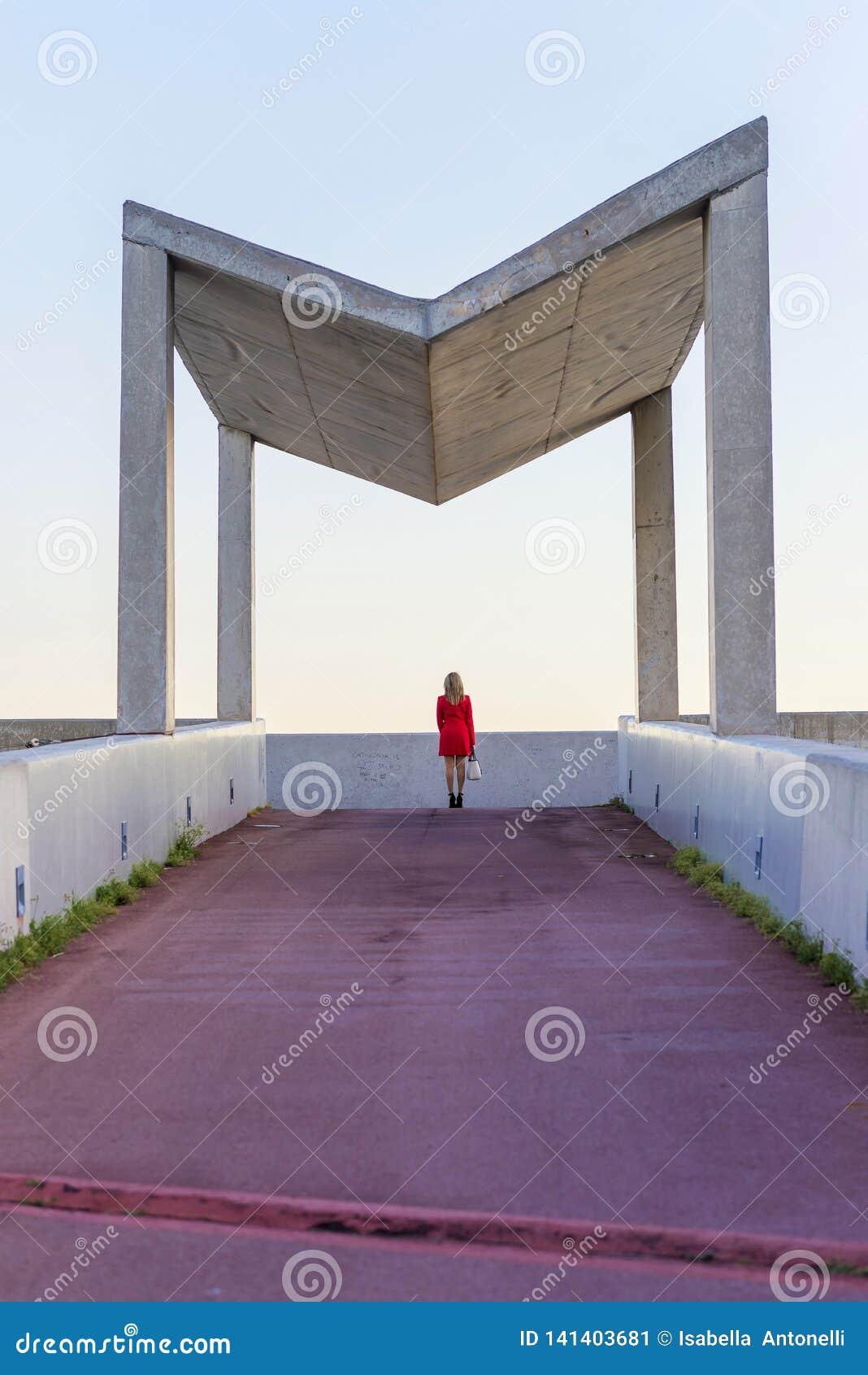 穿红色夹克,裙子和拿着一个白色提包的一名端庄的妇女的背面图,当站立在街道在一好日子时