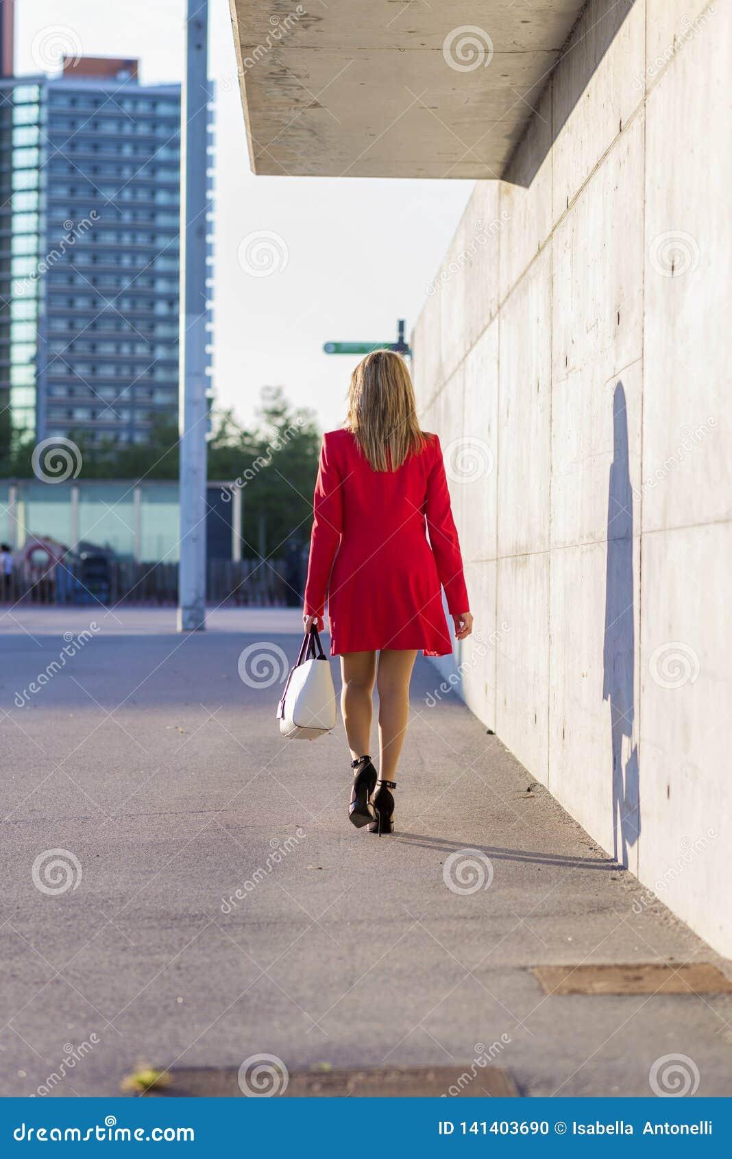 穿红色夹克,裙子和拿着一个白色提包的一名端庄的妇女的背面图,当走在街道在一好日子时
