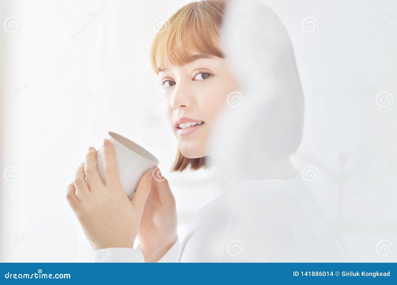 穿白色衬衫的妇女是微笑和拿着一杯咖啡
