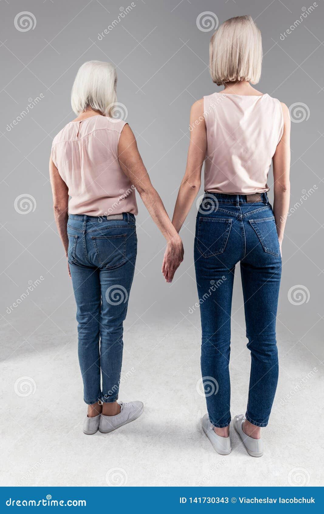 站立与她的老母亲和握她的手的白肤金发的短发女孩