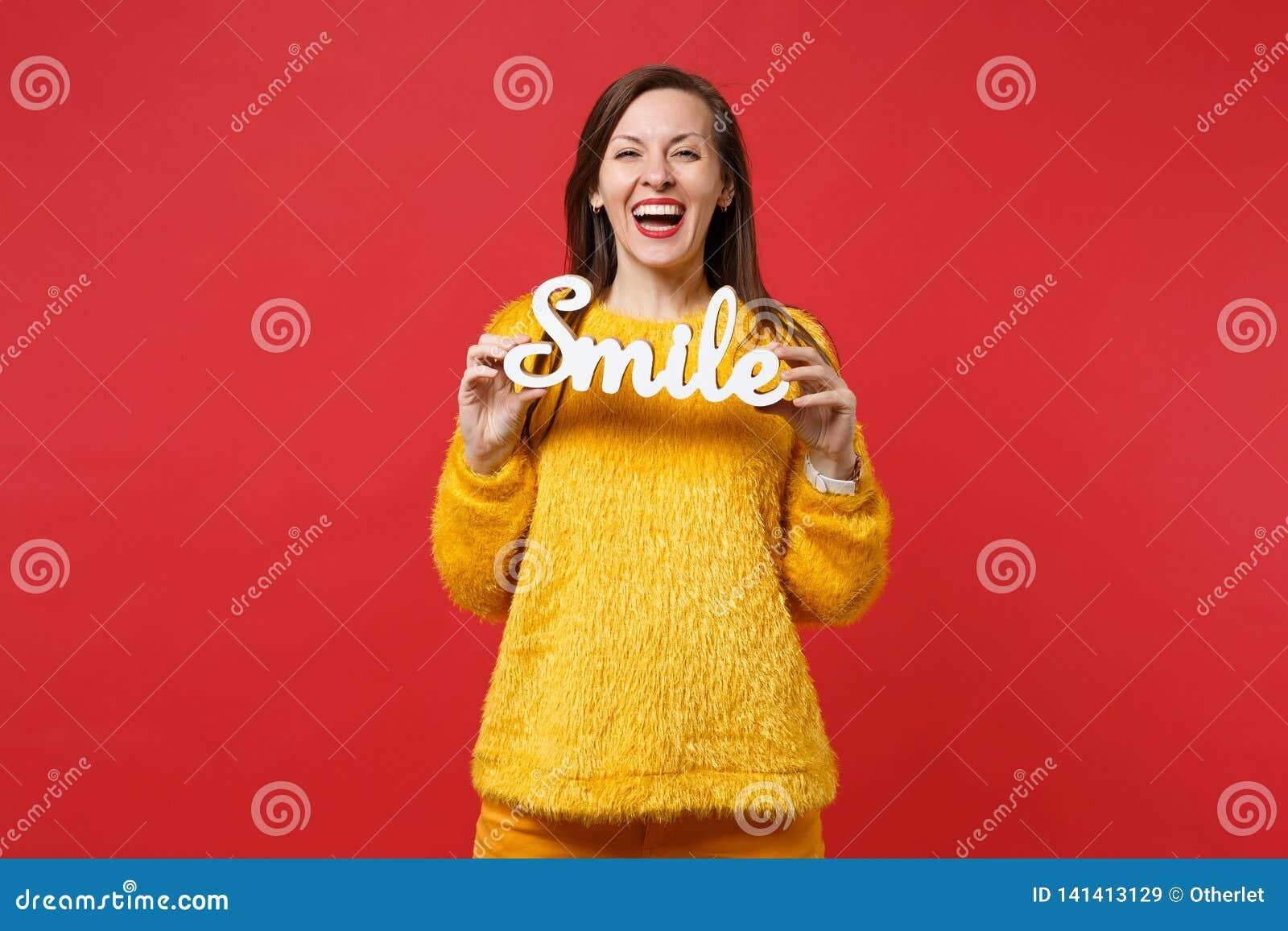 笑的年轻女人画象黄色毛皮毛线衣的拿着木词信件在明亮的红色墙壁上微笑隔绝