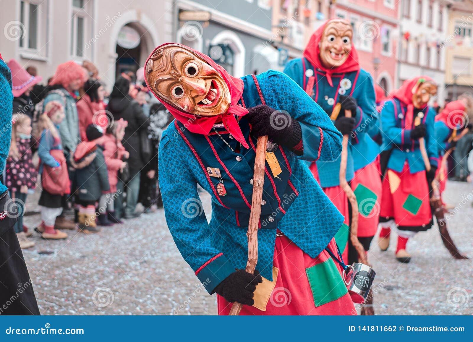 红色和蓝色服装的神仙的巫婆有弯的姿态的 街道狂欢节在德国南部-黑森林