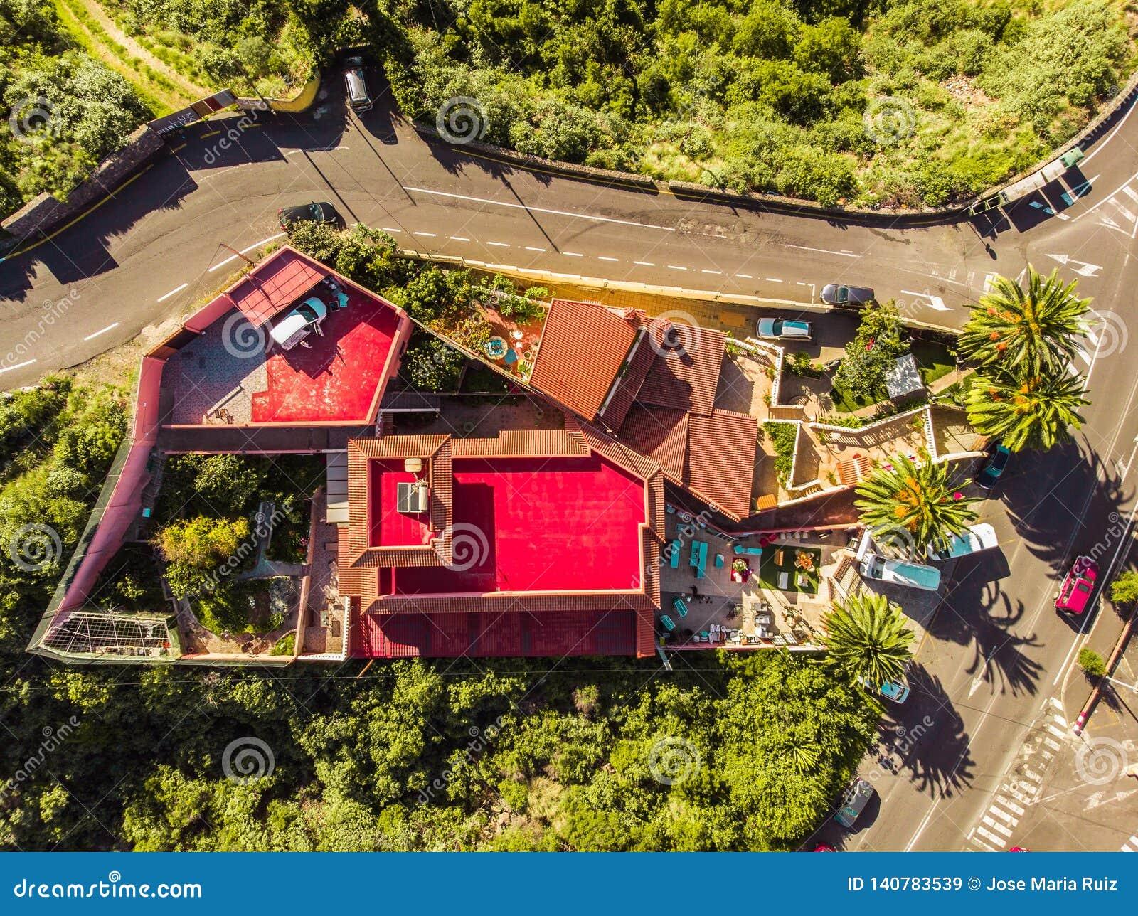 红色房子和大庭院射击由寄生虫 在边和棕榈的路在特内里费岛