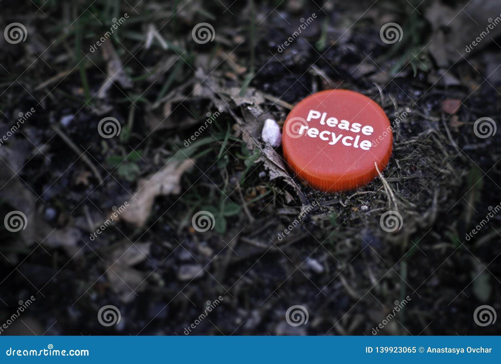 红色瓶盖与'请回收'讽刺地说谎在草地面的消息在公园中间 回收概念