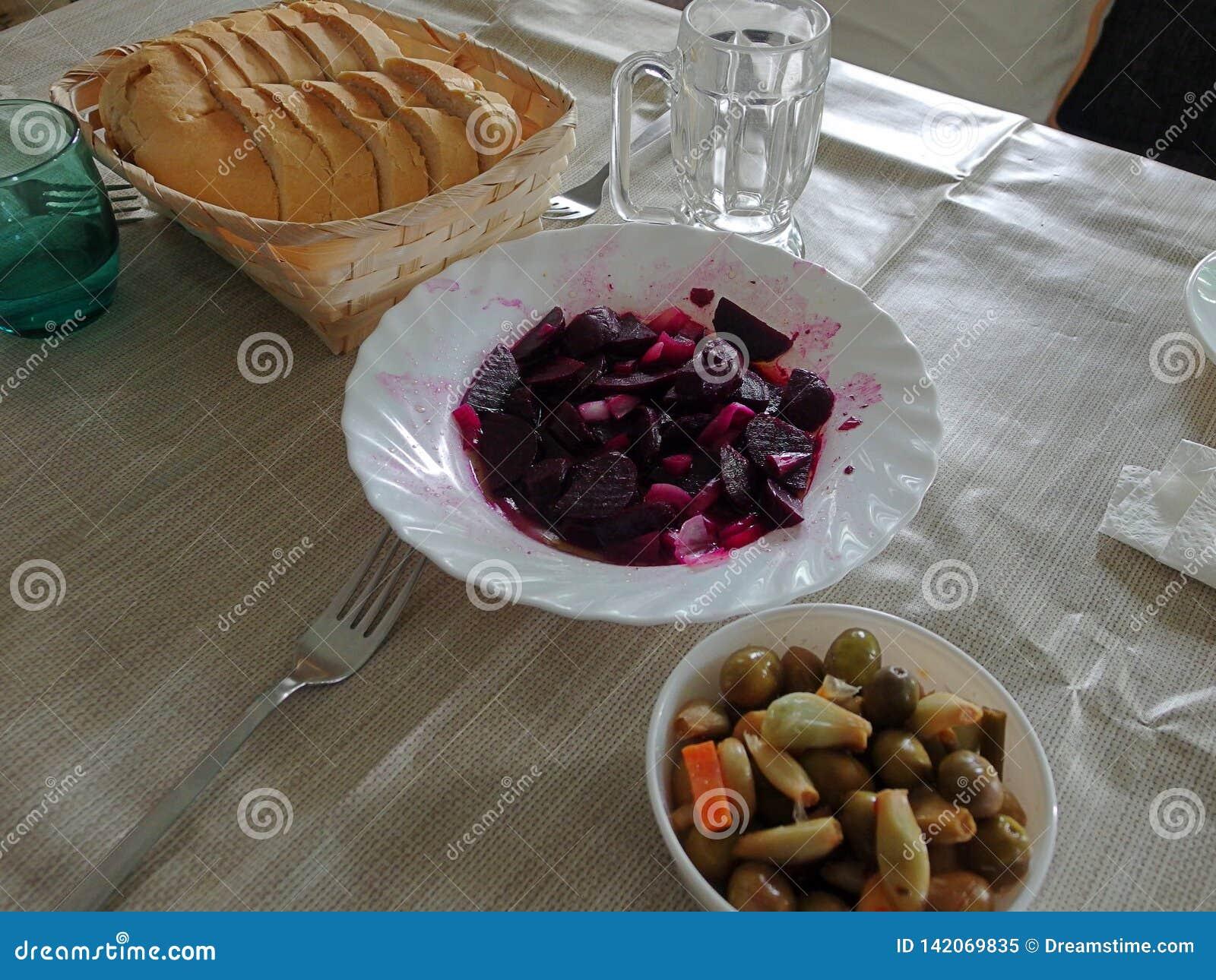 红色甜菜和橄榄用面包在桌上