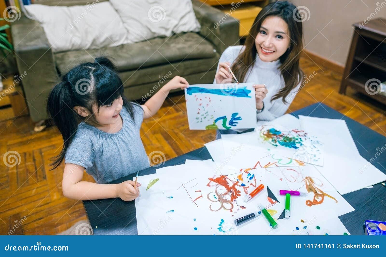 绘与母亲的逗人喜爱的女孩一幅画和在家显示她的工作