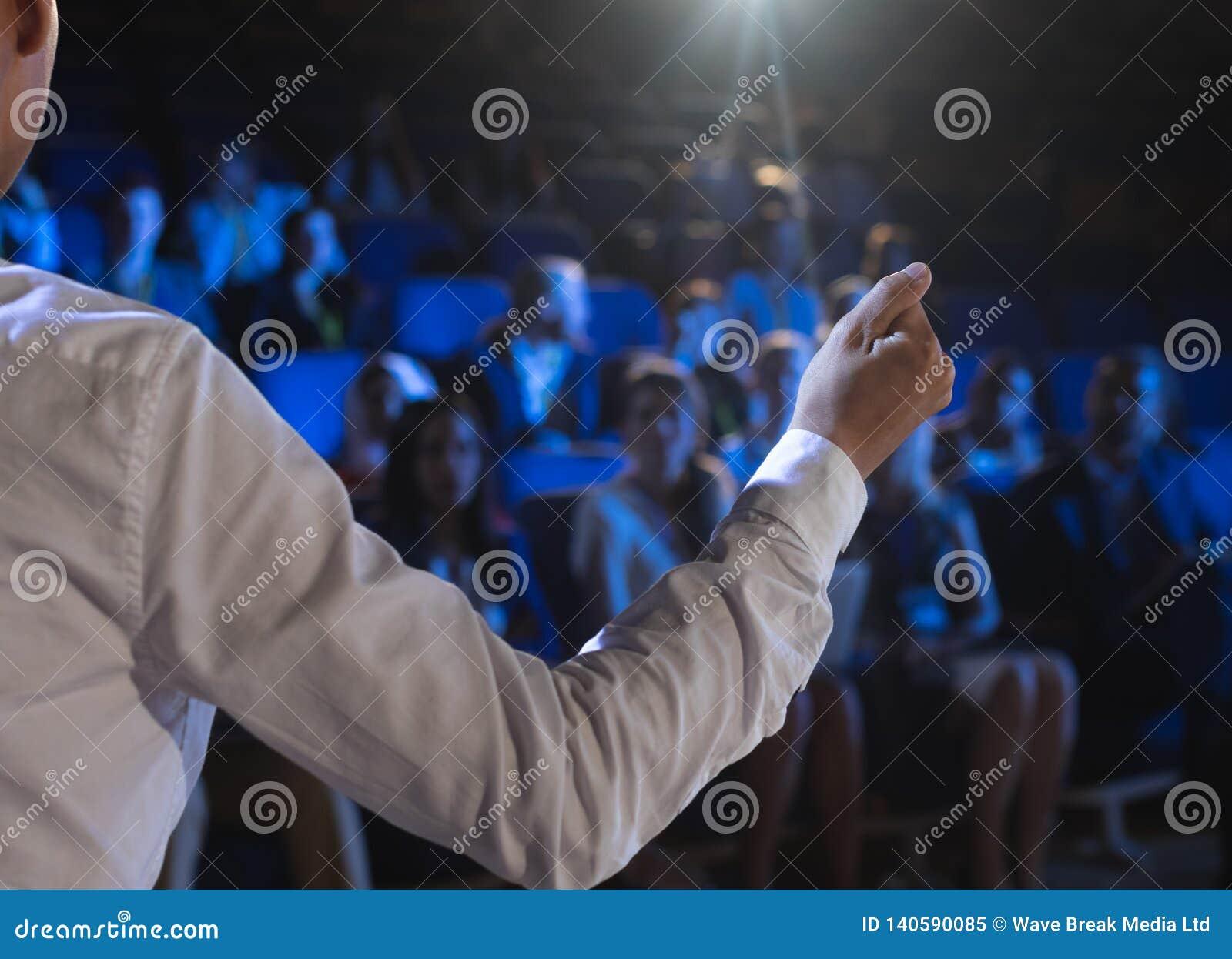 给在观众前面的商人介绍在观众席
