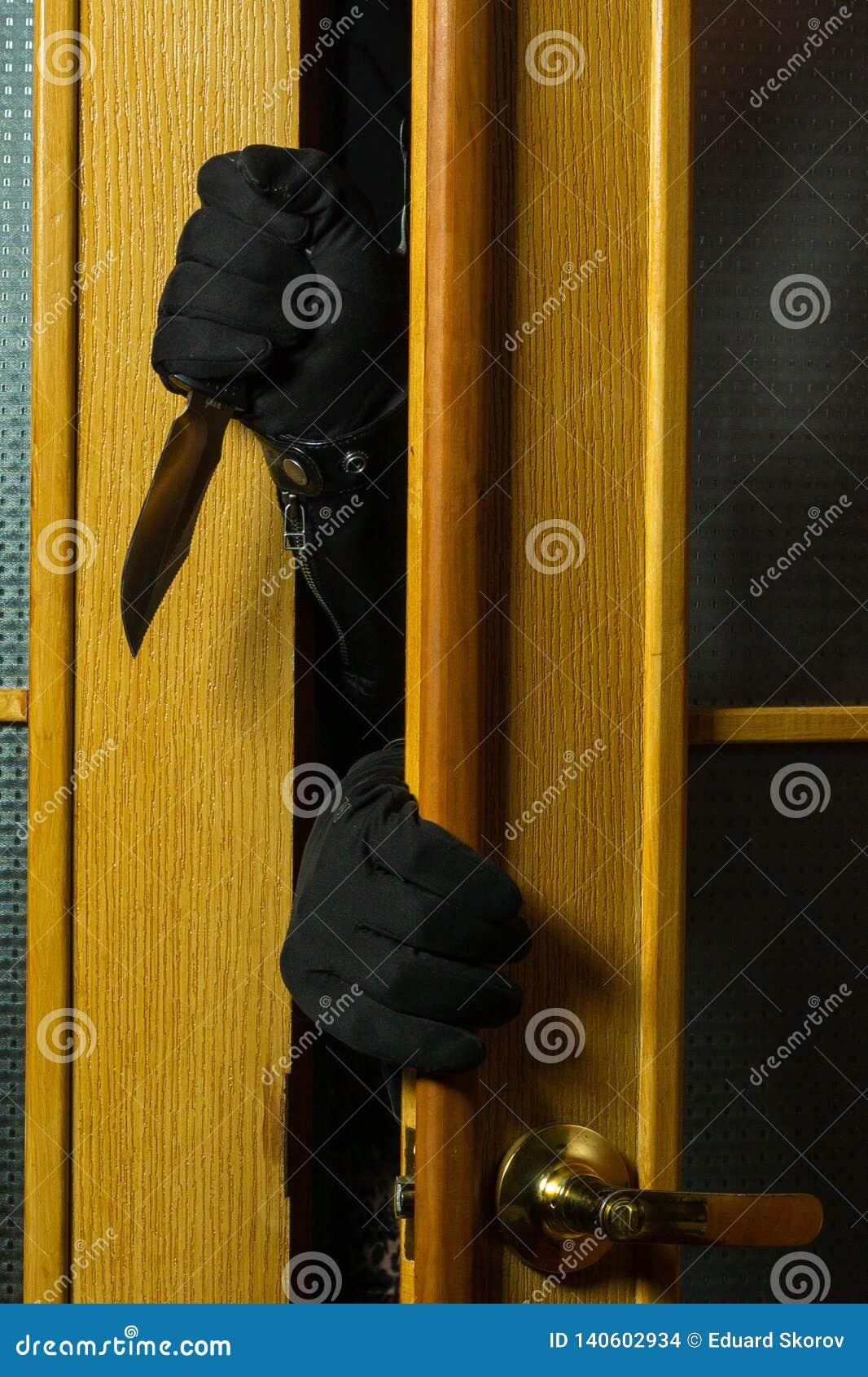 罪犯进入公寓 在黑手套和刀子的人的手