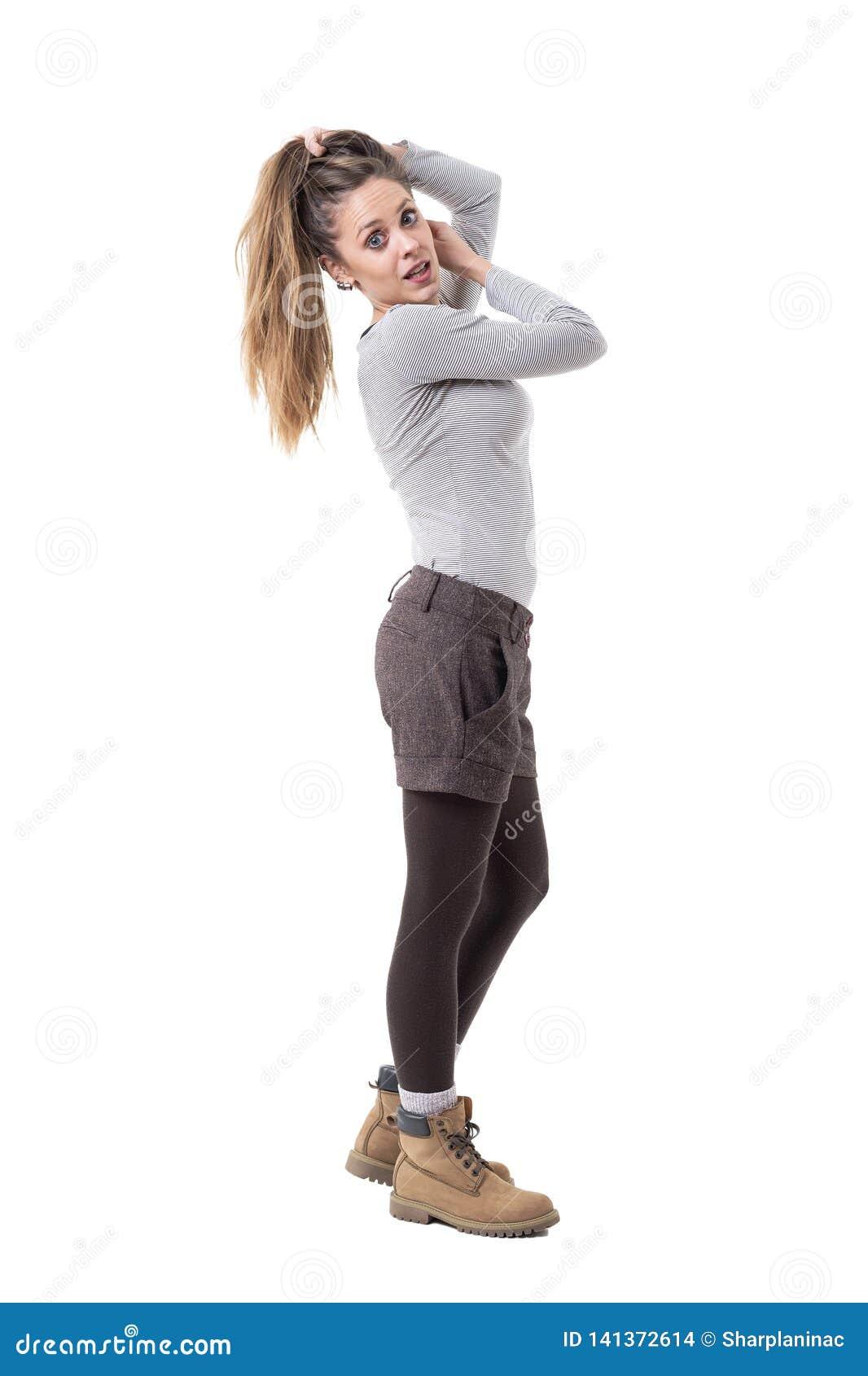 美丽的握在马尾的头发和摆在为照相机的年轻女人时髦的cutie