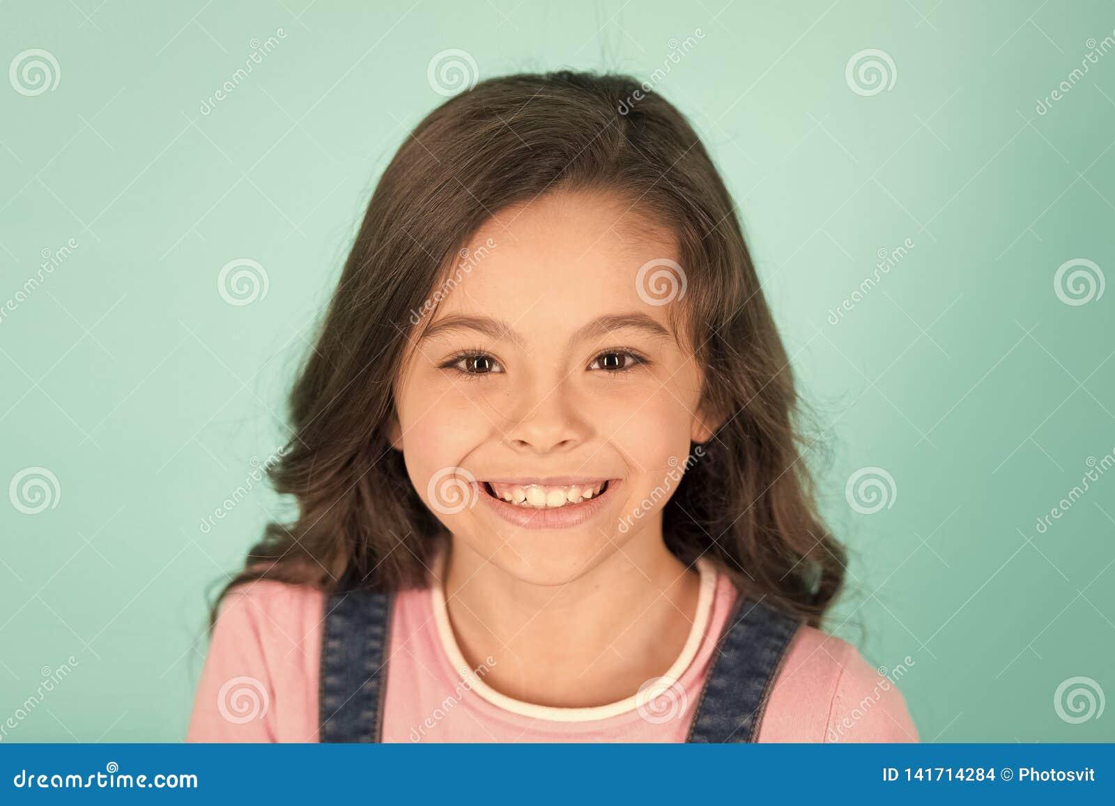 美好的微笑 儿童愉快快乐享受童年 女孩卷曲发型可爱的微笑的愉快的面孔 孩子迷住