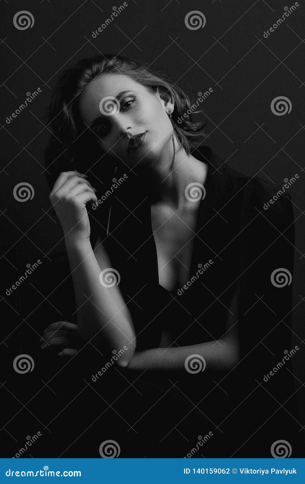 美妙的深色的女孩画象有摆在与对比光的波浪头发的 黑白定调子