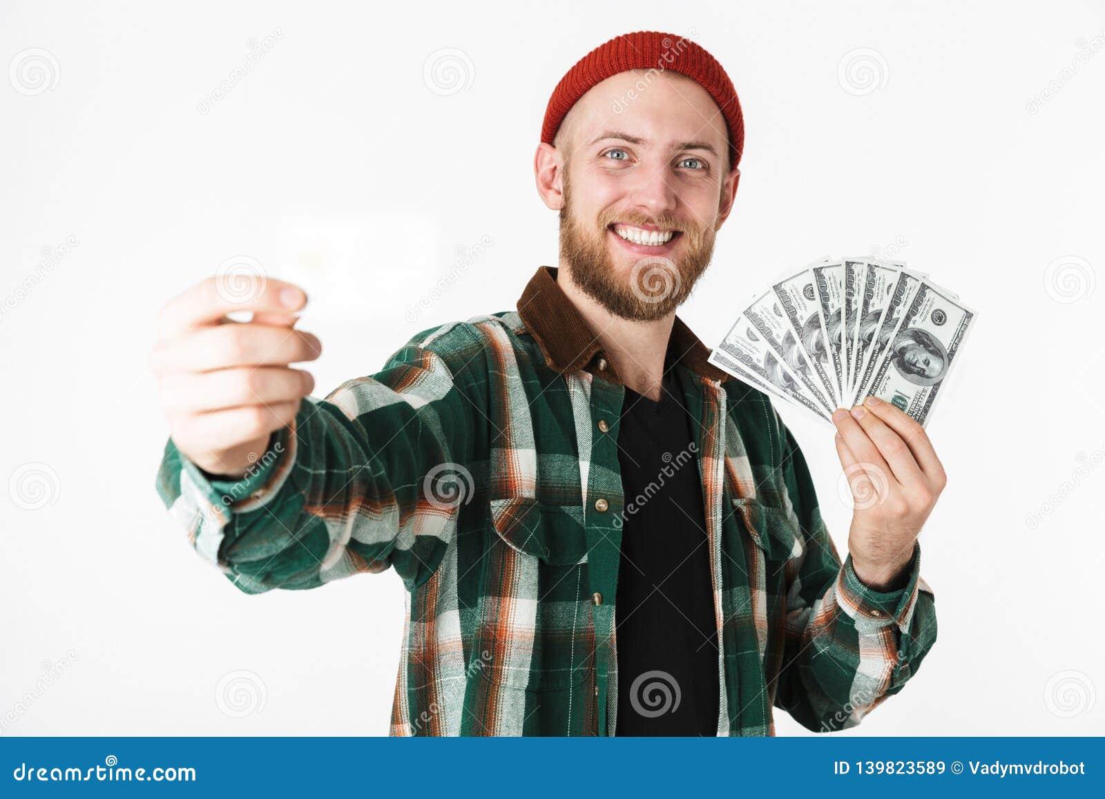 美元金钱的帅哥拿着信用卡的图象和爱好者的,当站立隔绝在白色背景时
