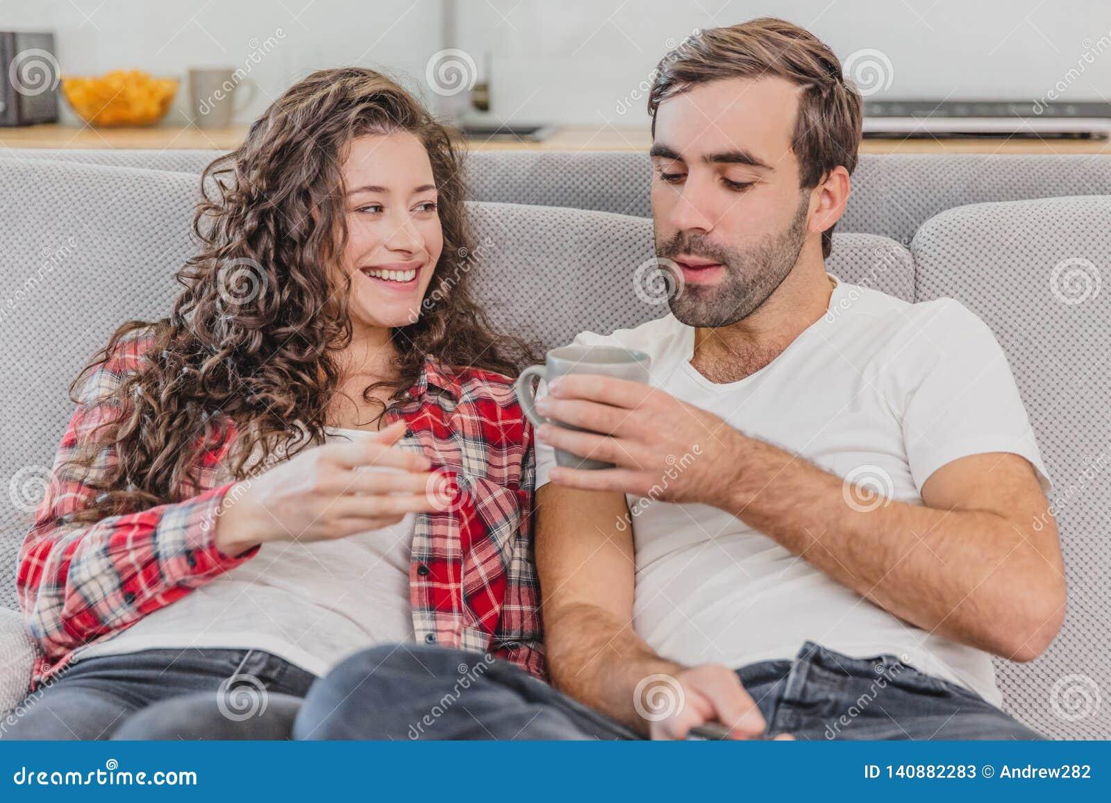 真的爱 快乐的浪漫夫妇坐在一舒适屋子和微笑的长沙发