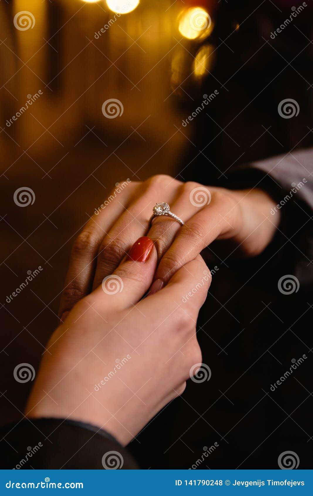 现实提案:新娘的朋友检查定婚戒指-与一颗大宝石的一个圆环