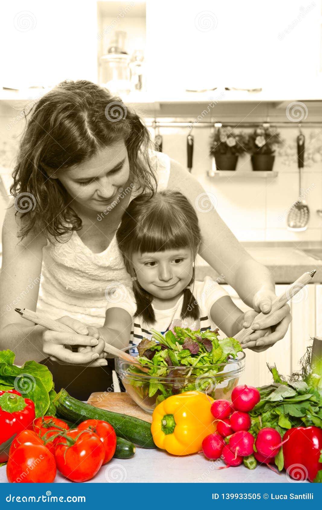 烹调晚餐的母亲和女儿在厨房里