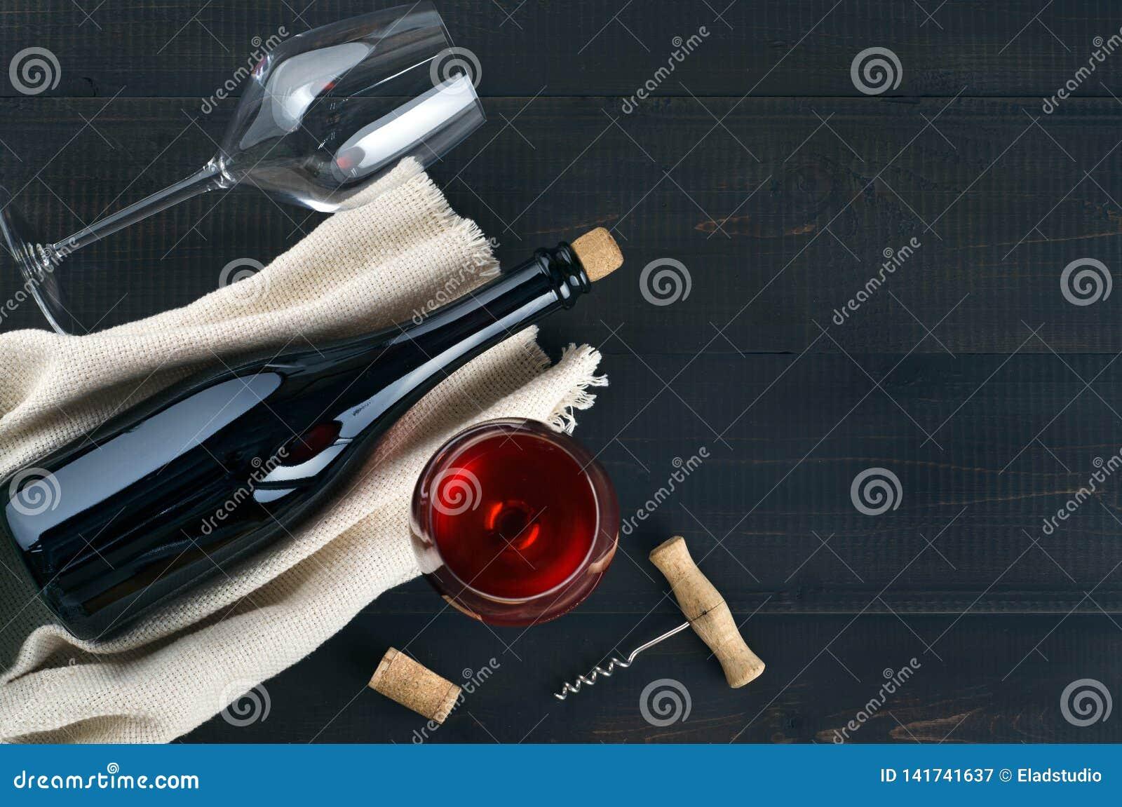 瓶、酒杯和拔塞螺旋在黑暗的桌上