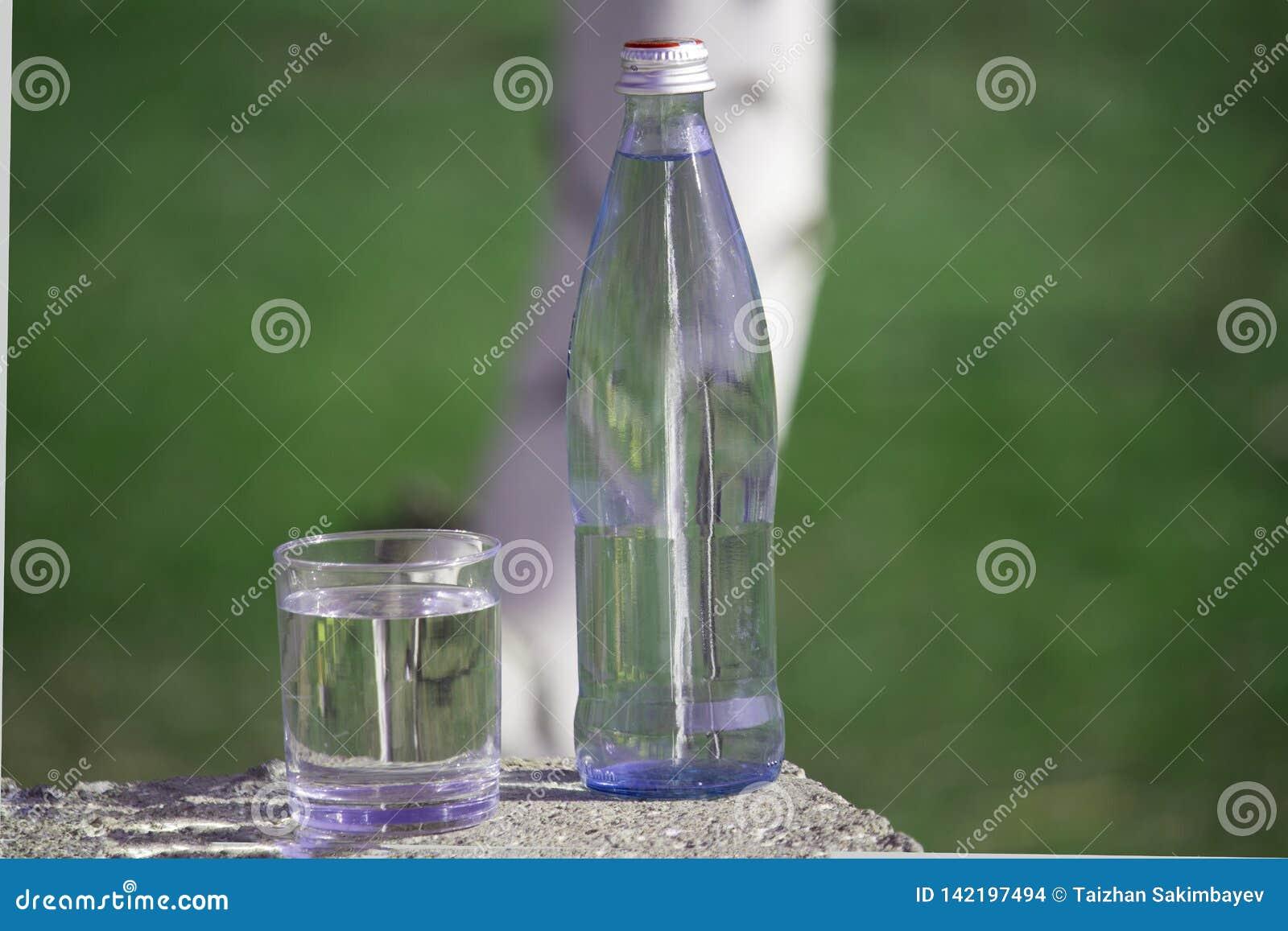 瓶和玻璃与淡水在草背景