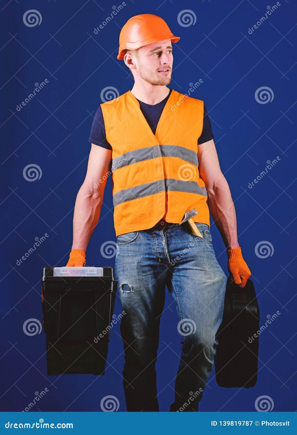 盔甲的人,安全帽拿着工具箱和手提箱有工具的,蓝色背景 专业安装工概念 杂物工