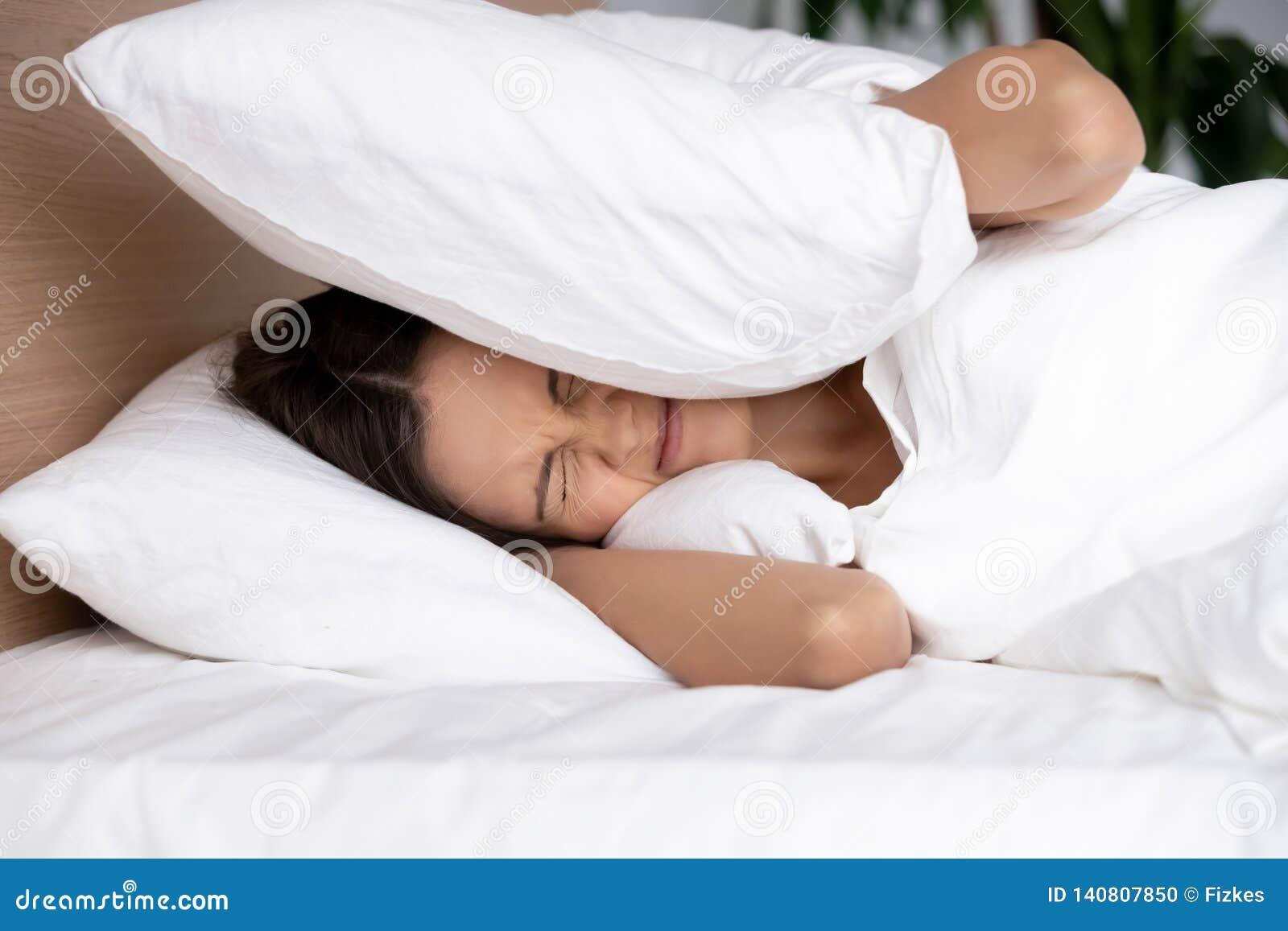 盖耳朵的懊恼年轻女人用枕头,遭受噪声