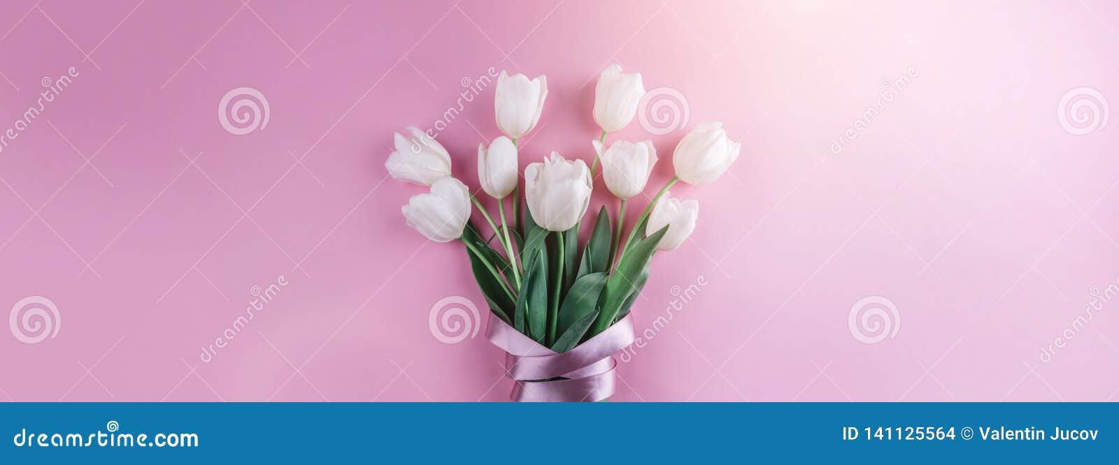 白色郁金香花花束在桃红色背景的 卡片为母亲节,复活节快乐3月8日, 等待的春天