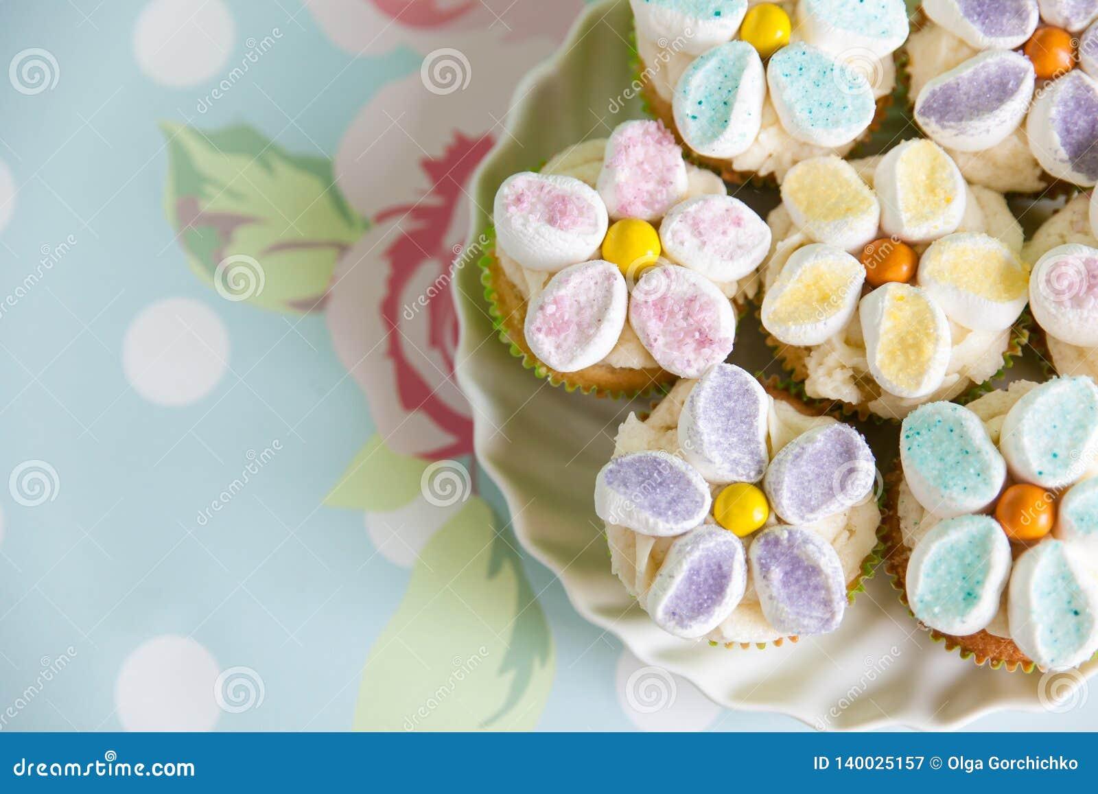 用黄油奶油和蛋白软糖花装饰的杯形蛋糕