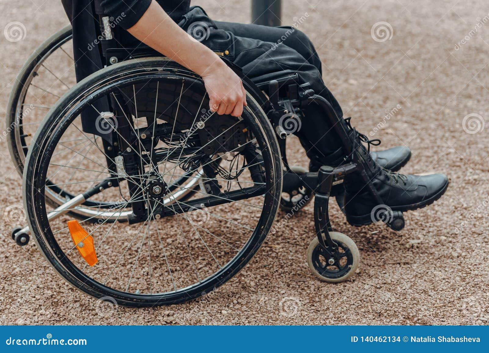 男性手特写镜头在轮椅轮子的在步行期间的在公园