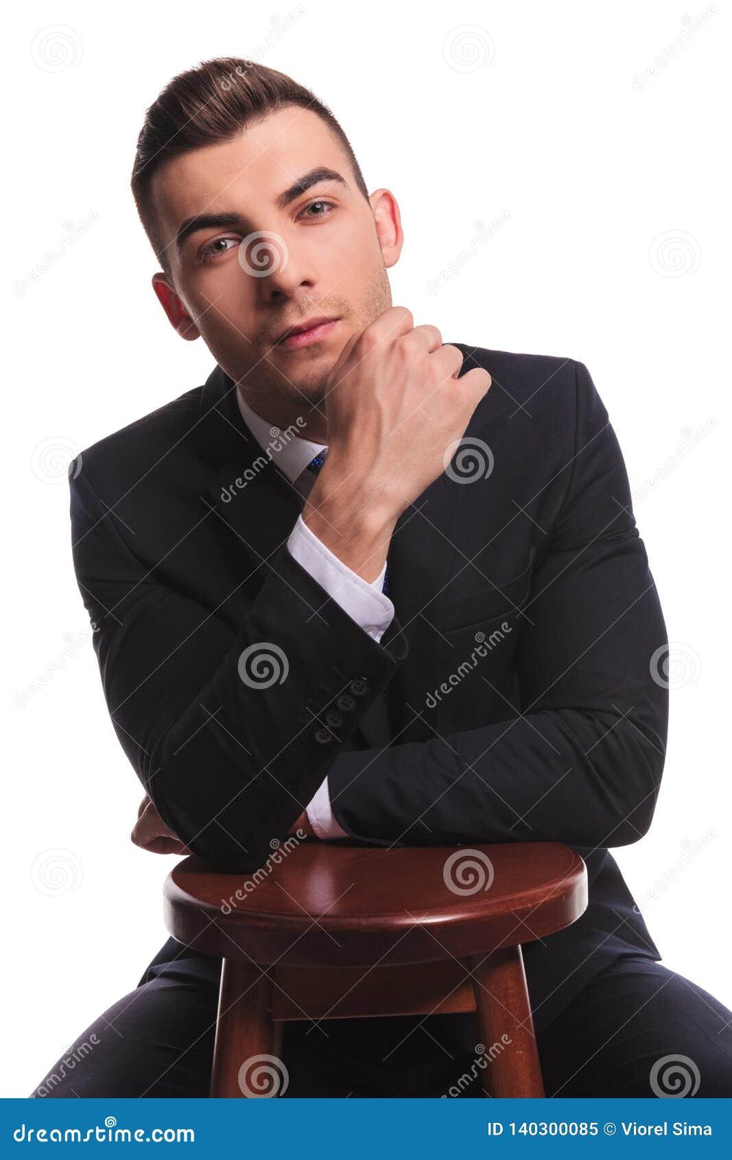 衣服的可爱的人用在椅子的手