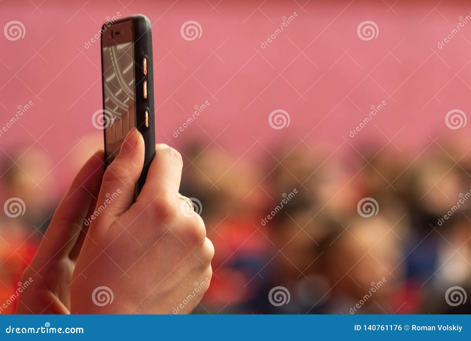 被弄脏的背景 报告文学照片或录影射击在一个手机 女孩举行智能手机在selfie方式或广播下