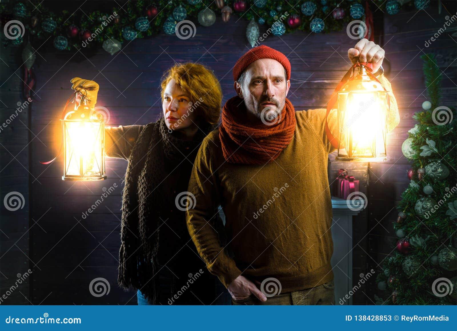 详细检查房子的被集中的夫妇,当使用手灯笼时